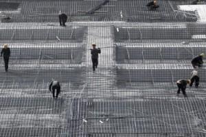 Obreros chinos trabajan en la preparación del encofrado de un edificio en la capital. Fuente: Zinias